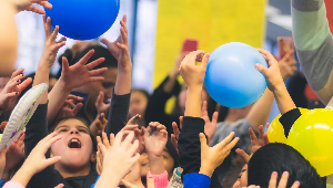 Image of kids reaching for balloons